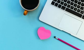 Heart-shaped notepad and coffee sitting at a business woman's desk