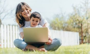 Mom working outdoors on laptop with son.