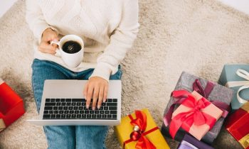 Woman working online during the holidays, among Christmas gifts.