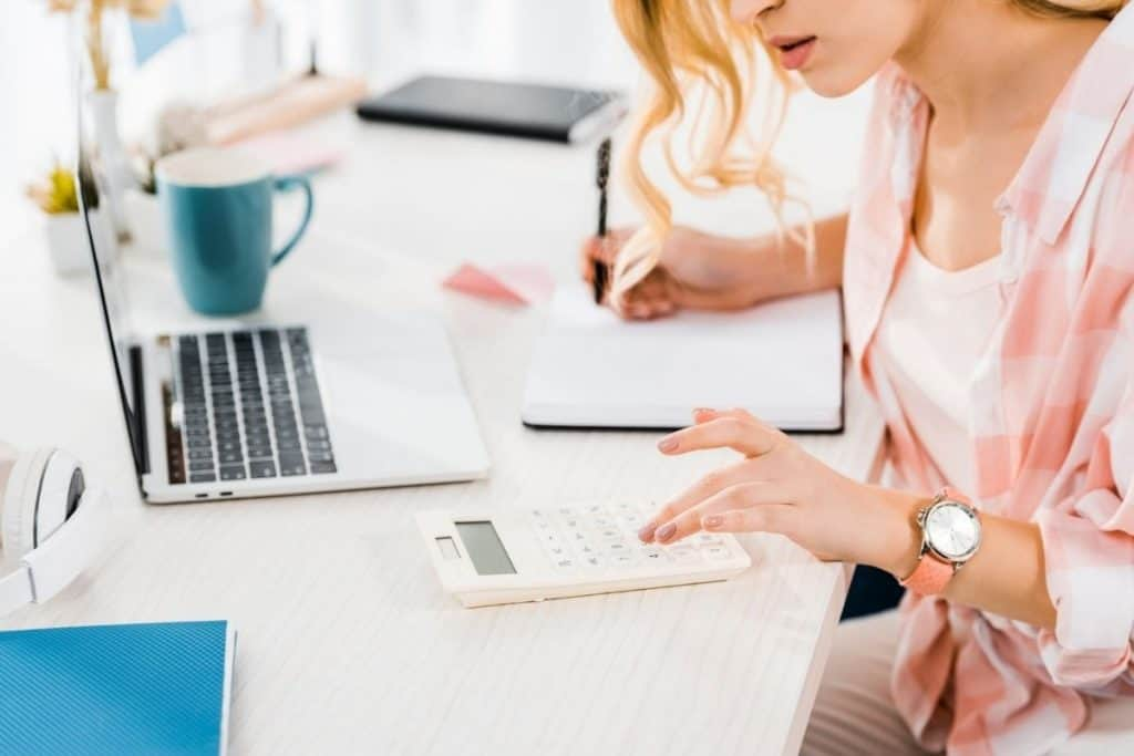 Woman sitting in home office, using a calculator and working on a budget