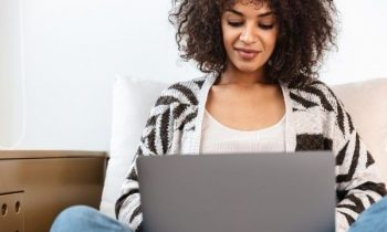 Woman writing on laptop at home.