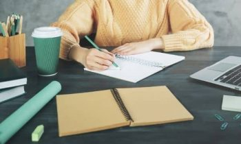 Woman writing at desk in home office to make money from home