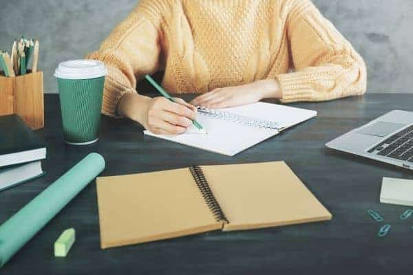 Woman writing at desk in home office