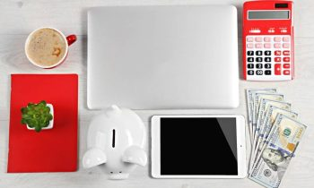 Still life shot of a work at home freelancer's desk, showing a laptop, calculator, and cash