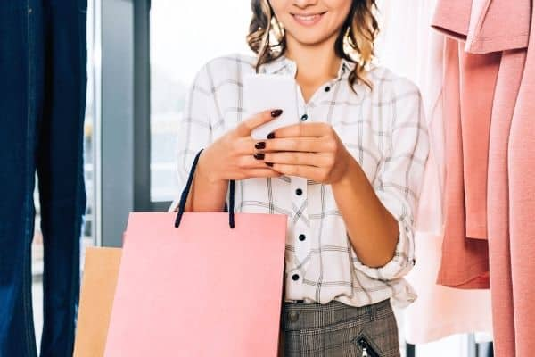 Woman using smartphone app while shopping - The Best Apps That Pay You for Receipts