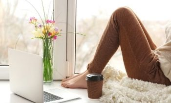 Woman sitting at home on window sill, working on laptop.