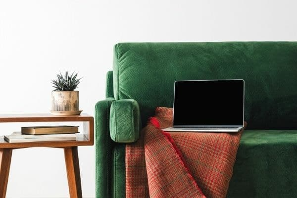 Laptop sitting on sofa in stylish living room.