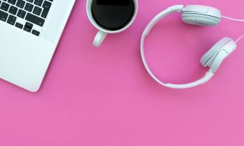 pink office area with laptop, coffee, and headphones - work at home job board